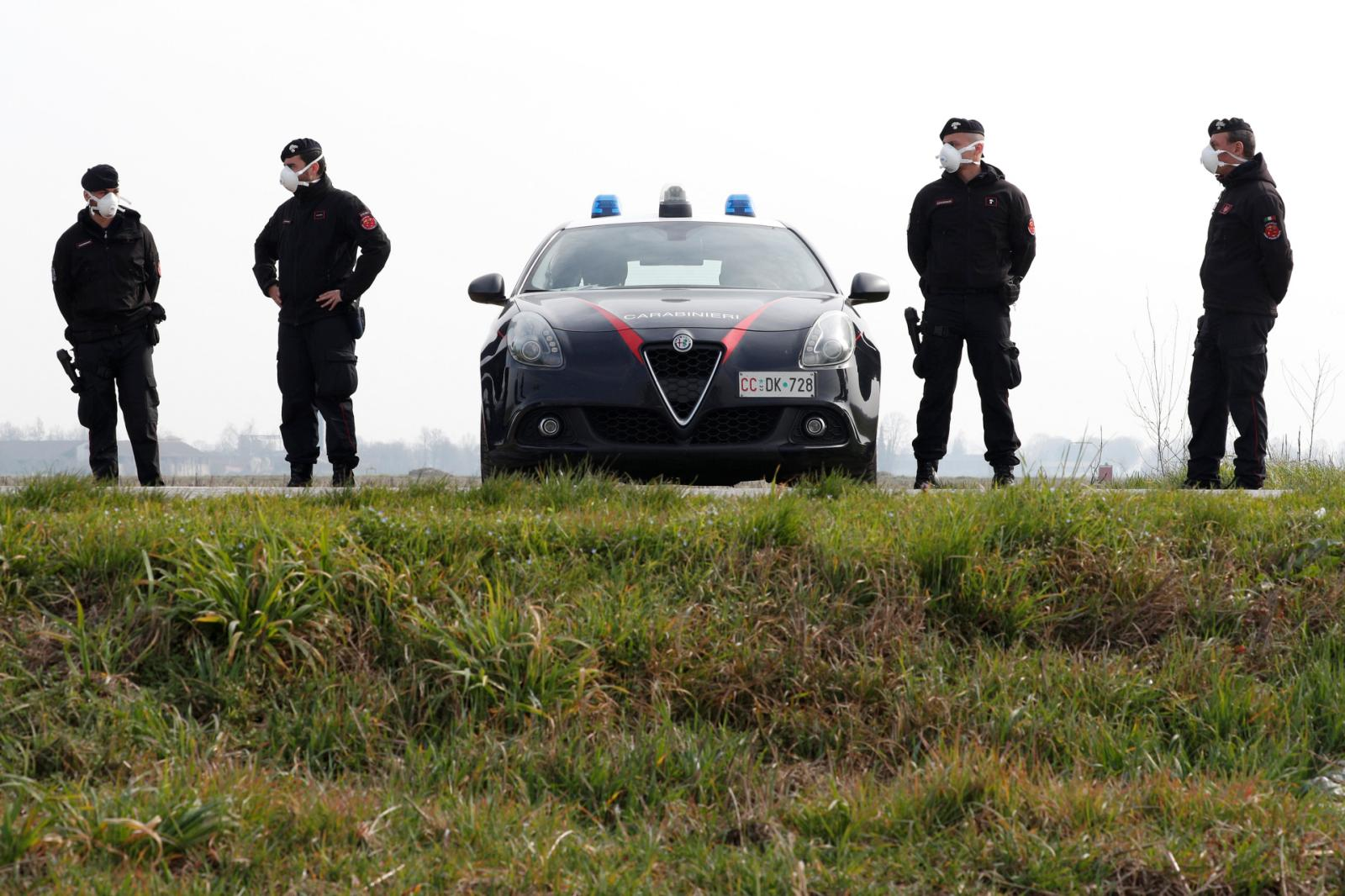 Carabinieri officers patrol outside the town of Castiglione D'Adda, which has been closed by the Italian government due to a coronavirus outbreak, Italy, February 23, 2020. REUTERS/Guglielmo Mangiapane